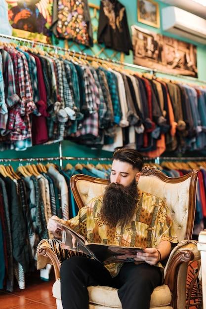 Portrait, de, a, homme barbu, reposer fauteuil antique, regarder magazine, dans, magasin vêtements Photo gratuit