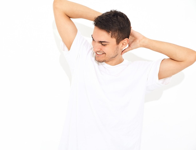 Portrait D'un Homme Beau Jeune Mannequin Souriant Vêtu De Jeans Et T-shirt Posant. Toucher Sa Tête Photo gratuit