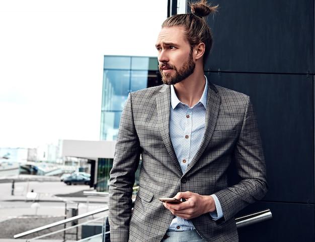 Portrait D'un Homme Beau Sexy Vêtu D'un élégant Costume à Carreaux Gris Photo gratuit