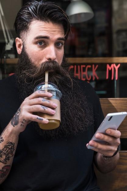 Portrait, homme, boire, lait chocolat, tenue, téléphone portable, dans main Photo gratuit