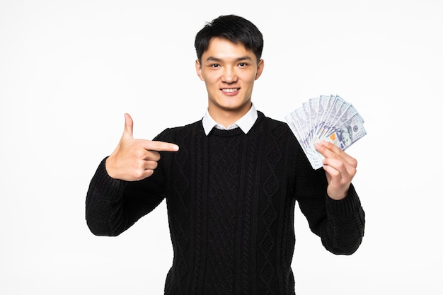 Portrait D'homme Chinois Excité Pointe Sur De Nombreux Billets Isolés Sur Mur Blanc Photo gratuit
