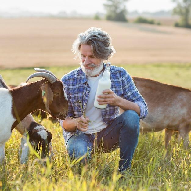 Portrait Homme à Côté De Chèvres Avec Une Bouteille De Lait Photo gratuit