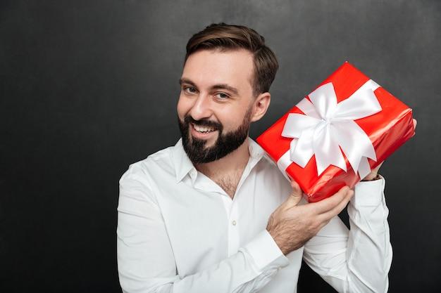 Portrait D'un Homme Curieux Secouant Une Boîte-cadeau Rouge Et Essayant De Reconnaître Ce Qu'il Y A à L'intérieur Sur Un Mur Gris Foncé Photo gratuit