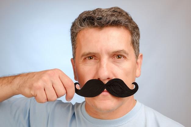 Portrait D'un Homme Avec Une Fausse Moustache à La Main Pour Assister à Un événement En Novembre Afin D'aider Les Hommes à Prendre Conscience Des Problèmes De Santé. Photo Premium