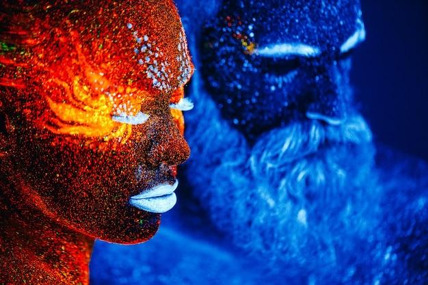 Portrait d'un homme et d'une femme barbus peints dans une poudre ultraviolette. Photo Premium