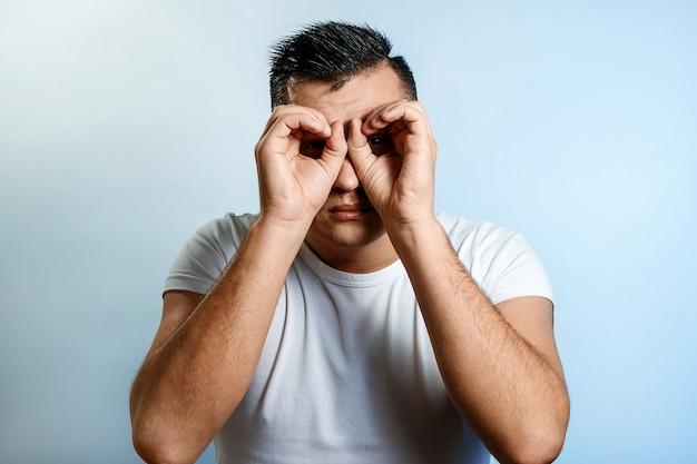 Portrait D'un Homme Sur Un Fond Clair, Fabrique Des Jumelles Avec Les Mains, Clairvoyant. Photo Premium