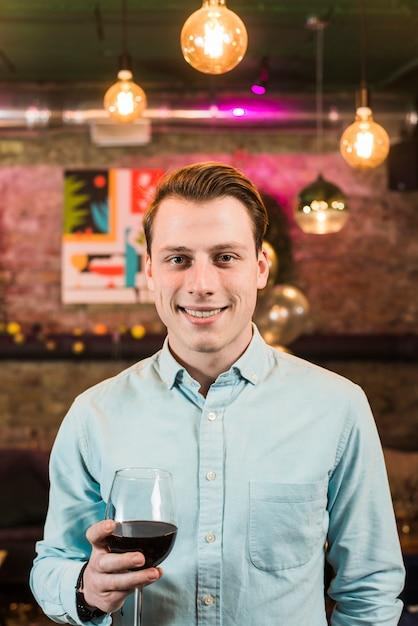 Portrait d'un homme heureux avec un verre de vin en boite de nuit Photo gratuit