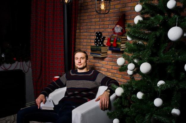 Portrait D'un Homme Avec Un Livre Assis Sur Une Chaise Contre L'arbre De Noël Avec Des Décorations. Photo Premium