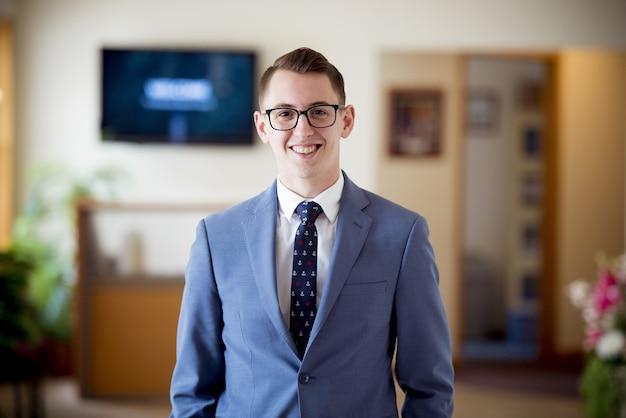 Portrait D'un Homme à Lunettes Dans Un Costume Bleu Avec Une Cravate Sous Les Lumières Avec Un Arrière-plan Flou Photo gratuit