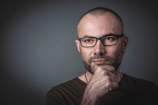 Portrait d'un homme avec des lunettes et la main sur le menton. Photo Premium