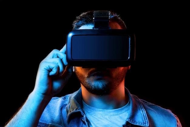 Portrait d'un homme à lunettes de réalité virtuelle, vr, sur un fond sombre. Photo Premium