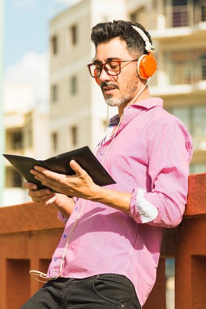 Portrait, de, a, homme moderne, debout, contre, mur, écoute, musique, sur, casque lecture, livre Photo gratuit