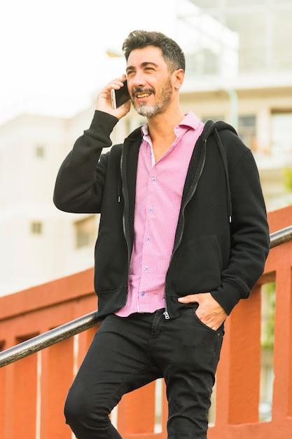 Portrait, de, homme moderne, main, poche, parler, sur, téléphone portable Photo gratuit