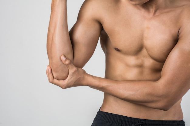 Portrait d'un homme muscle ayant des douleurs au coude isolé sur fond blanc Photo gratuit