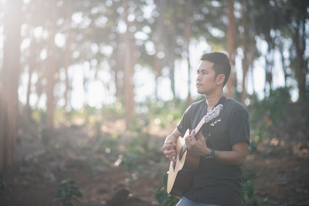 Portrait Homme Musicien Avec Guitare à La Forêt Photo Premium