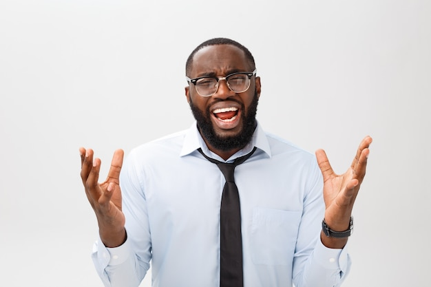 Portrait d'un homme noir agacé désespéré hurlant de colère et de colère lui arrachant les cheveux tout en se sentant furieux et en colère contre quelque chose Photo Premium