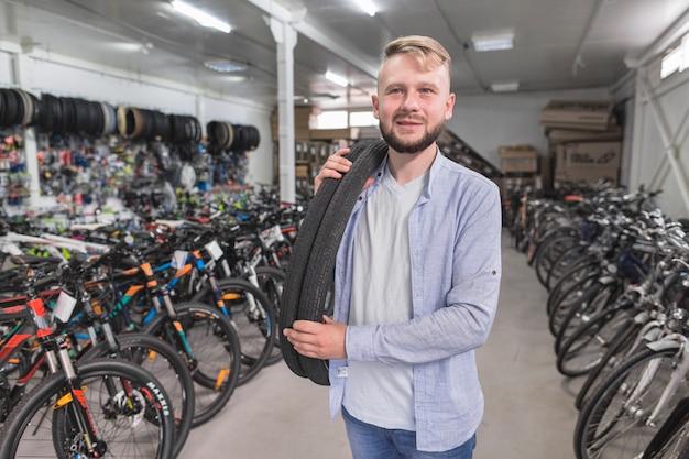 Portrait d'un homme avec des pneus de vélo dans le magasin Photo gratuit