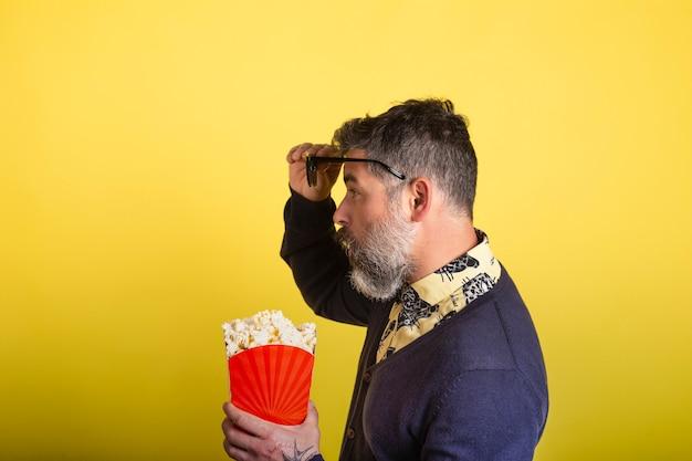 Portrait D'un Homme Séduisant Avec Barbe Et Lunettes De Soleil Tenant Une Boîte De Pop-corn De Profil Dans L'appareil Photo étonné En Regardant Les Lunettes Sur Fond Jaune. Photo Premium