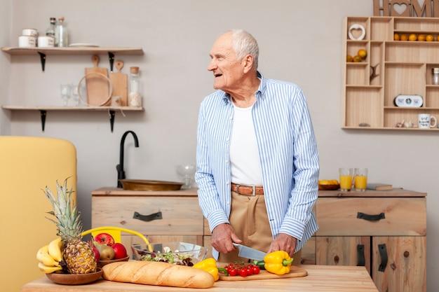 Portrait D'homme Senior, Couper Les Légumes Photo gratuit