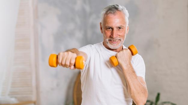 Portrait d'un homme senior heureux, soulever des poids Photo gratuit