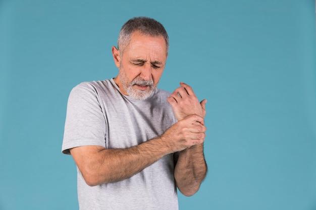 Portrait d'un homme senior tenant son poignet blessé Photo gratuit