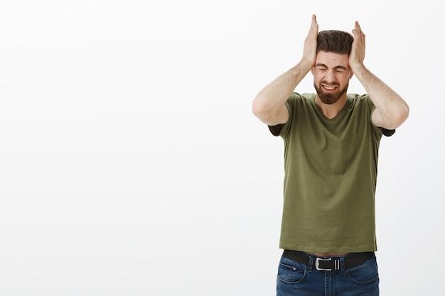 Portrait D'homme Souffrant D'énormes Maux De Tête Ou Migraine Saisissant La Tête Avec Les Deux Mains Plissant Les Yeux De La Douleur Et De La Détresse étant Bouleversé Et Stressé Debout Sur Un Mur Blanc Malheureux Photo gratuit