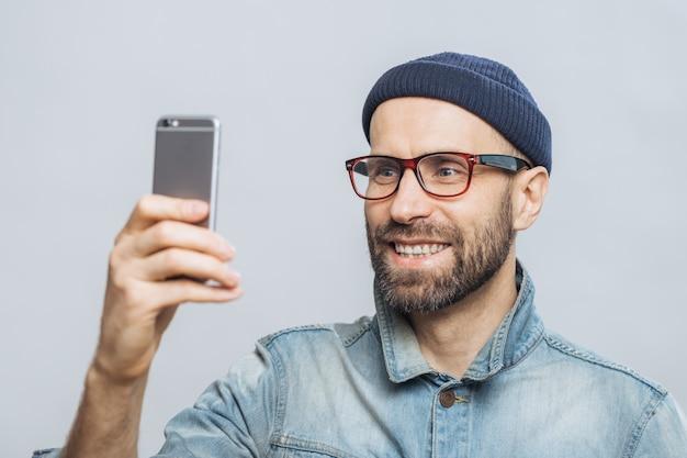 Portrait d'un homme souriant d'âge moyen heureux porte une veste en jean, un chapeau et des lunettes Photo Premium
