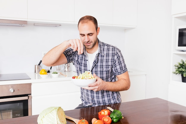 Portrait d'un homme souriant, ajoutant des épices dans une salade Photo gratuit
