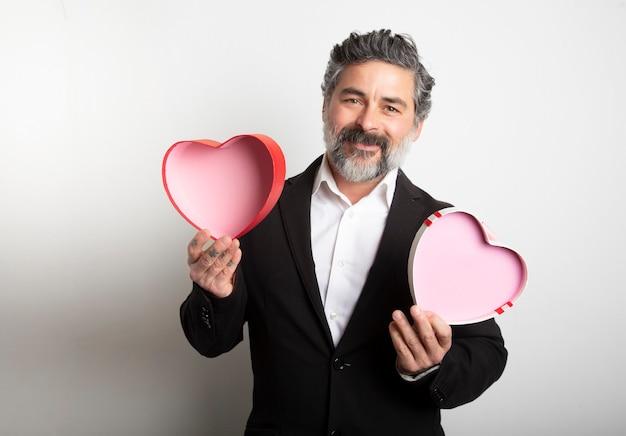 Portrait D'un Homme Souriant En Costume Avec Une Boîte En Forme De Coeur Sur Fond Blanc Photo Premium
