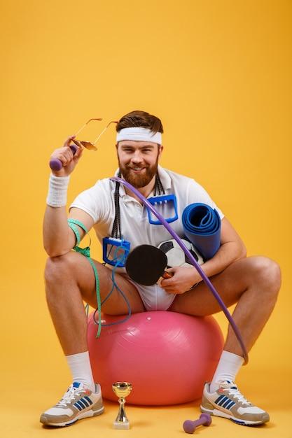 Portrait D'un Homme De Sport Assis Sur Un Ballon De Fitness Photo gratuit