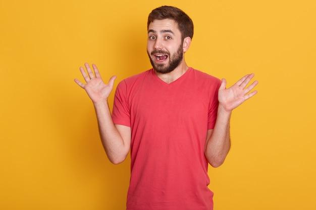 Portrait D'un Homme Surpris, Beau Mâle écartant Les Mains, Posant Isolé Sur Le Mur Jaune, Mec Mal Rasé Attrayant Portant Un T-shirt Décontracté Rouge. Le Concept Des émotions Humaines. Photo gratuit