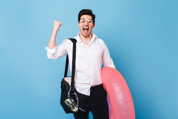 Portrait D'homme En Tenue D'affaires Appréciant Le Début Des Vacances. Guy Posant Avec Cercle Gonflable Contre L'espace Bleu. Photo gratuit