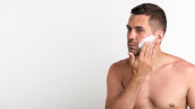 Portrait d'homme torse nu, application de mousse pendant le rasage Photo gratuit