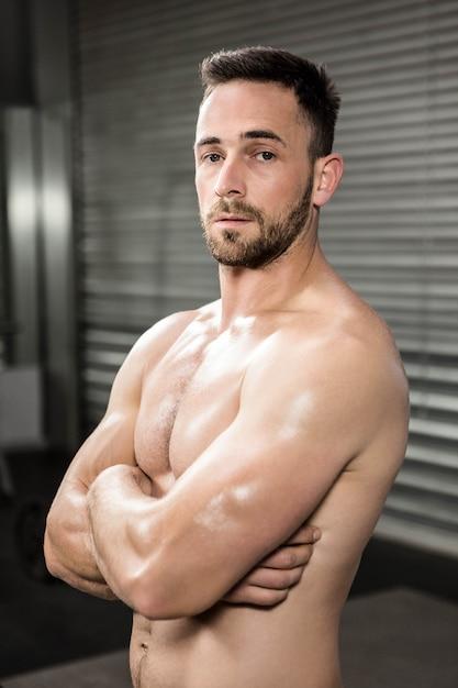 Portrait d'un homme torse nu avec les bras croisés à la salle de gym crossfit Photo Premium