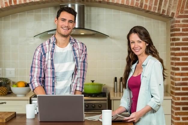 Portrait, homme, utilisation, ordinateur portable, et, femme, journal lecture, sur, worktop cuisine Photo Premium