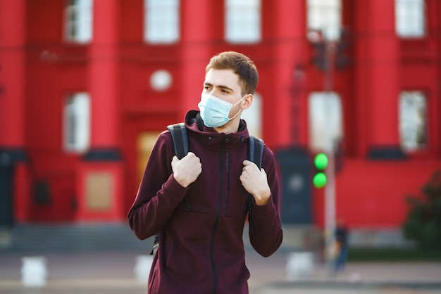 Portrait D'hommes En Masque Médical Stérile Protecteur Sur Son Visage Dans La Ville De Rue. Covid19. Photo Premium