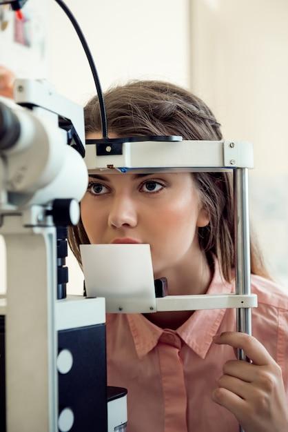 Portrait Horizontal De Femme Européenne Ciblée Testant La Vue Tout En Regardant à Travers Le Microbioscope, Assis Dans Un Bureau Spécialisé, Voulant Choisir Les Lunettes Appropriées Pour Mieux Voir Photo gratuit