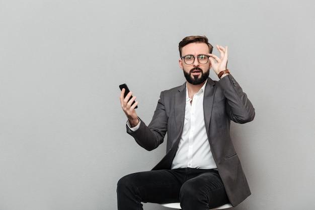 Portrait horizontal d'un homme sérieux à lunettes à la recherche sur l'appareil photo tout en étant assis sur une chaise et à l'aide de téléphone portable, isolé sur gris Photo gratuit