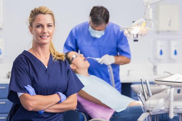 Portrait d'une infirmière souriante, les bras croisés et le dentiste avec le patient derrière lui Photo Premium