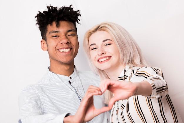 Portrait, de, interracial, jeune couple, sourire, forme coeur, à, mains Photo gratuit