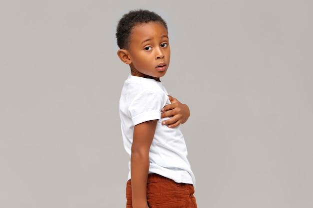 Portrait Isolé De Garçon à La Peau Sombre Perplexe Habillé En T-shirt Blanc .bel Enfant Africain Posant. Le Langage Du Corps Photo gratuit