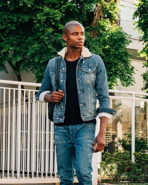 Portrait d'un jeune africain rasé avec sac à dos à l'extérieur Photo gratuit
