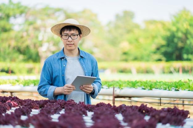Portrait De Jeune Agriculteur Intelligent à L'aide D'un Ordinateur Tablette Numérique Pour L'inspection. Photo Premium