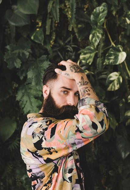 Portrait, jeune, barbu, tatouage, main Photo gratuit