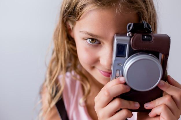 Portrait D'un Jeune Beau Gosse Tenant Un Appareil Photo Vintage Et Souriant. Fond Blanc. Les Enfants à L'intérieur. Concept De Photographie Photo Premium
