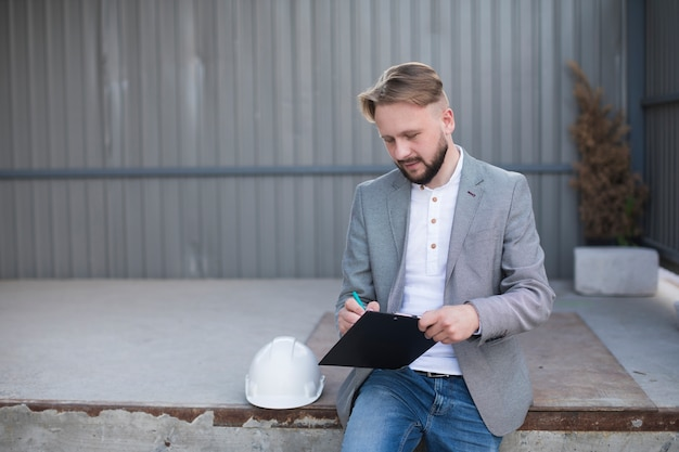 Portrait de jeune bel architecte écrit sur le presse-papiers en plein air Photo gratuit