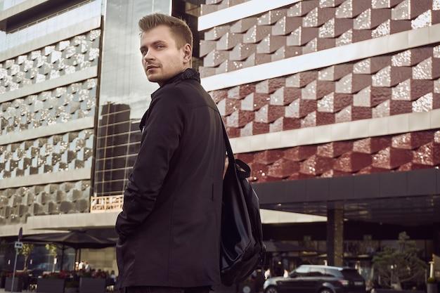 Portrait de jeune bel homme en manteau sombre avec sac dans la ville Photo Premium