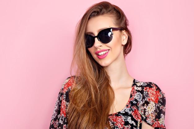 Portrait de jeune belle femme mince en robe sexy avec des lèvres sensuelles en portant des lunettes de soleil souriant et posant Photo Premium