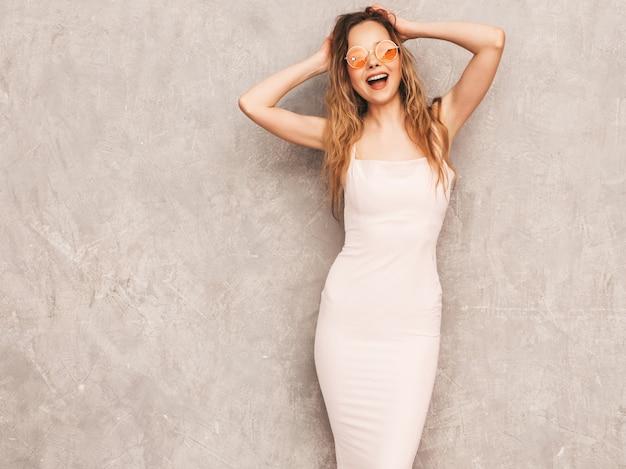 Portrait De Jeune Belle Fille Souriante En Robe Rose Pâle D'été à La Mode. Sexy Femme Insouciante Posant. Modèle Positif S'amusant Dans Des Lunettes De Soleil Rondes Photo gratuit