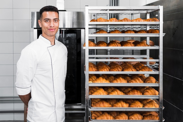 Portrait d'un jeune boulanger confiant debout près des étagères de croissants Photo gratuit